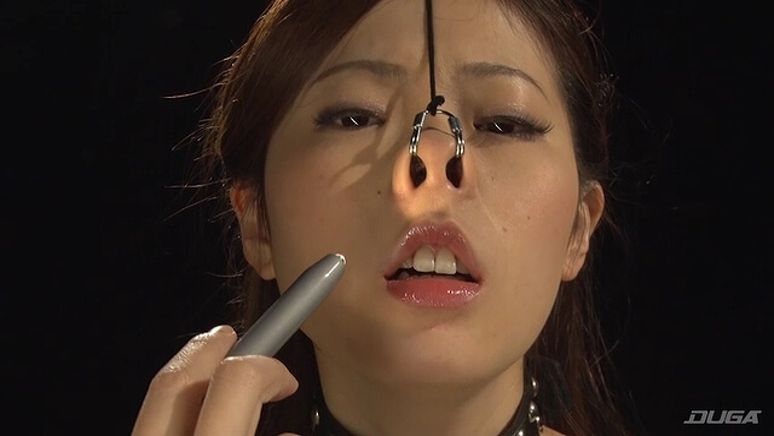 鼻フックされ鼻にライトをあてられるお姉さん
