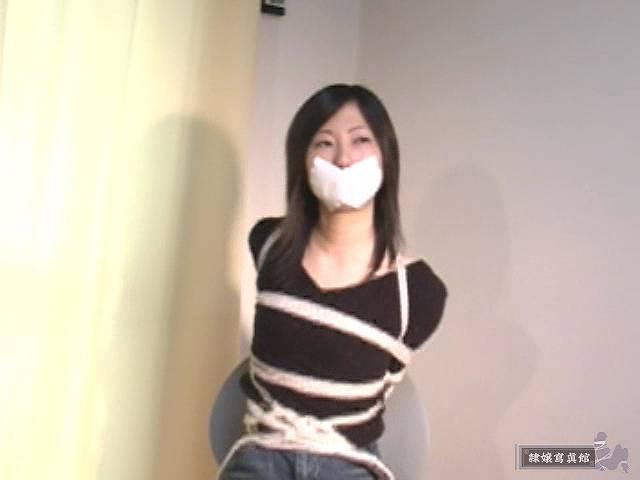 白色のガムテープで口をふさがれる相田ななこ